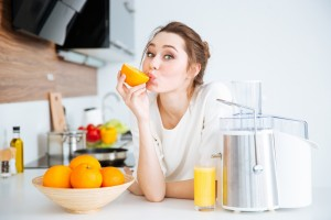 Cute charming woman making juice and eating oranges